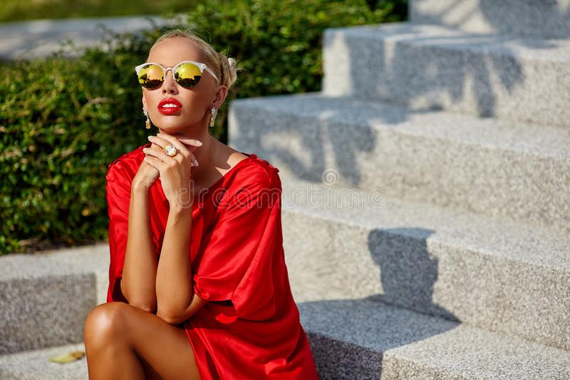 Fashion portrait of stylish rich woman in red dress and sunglass. Es stock images