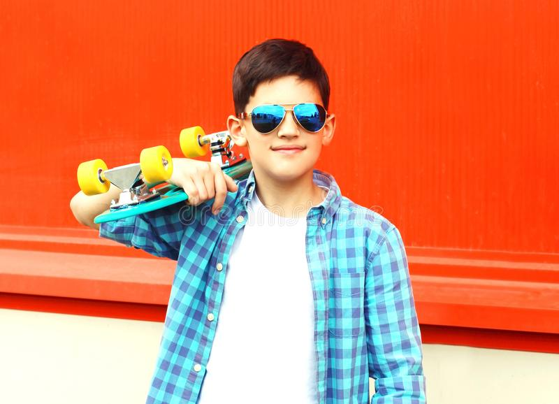 Fashion portrait teenager boy holds a skateboard in sunglasses royalty free stock images