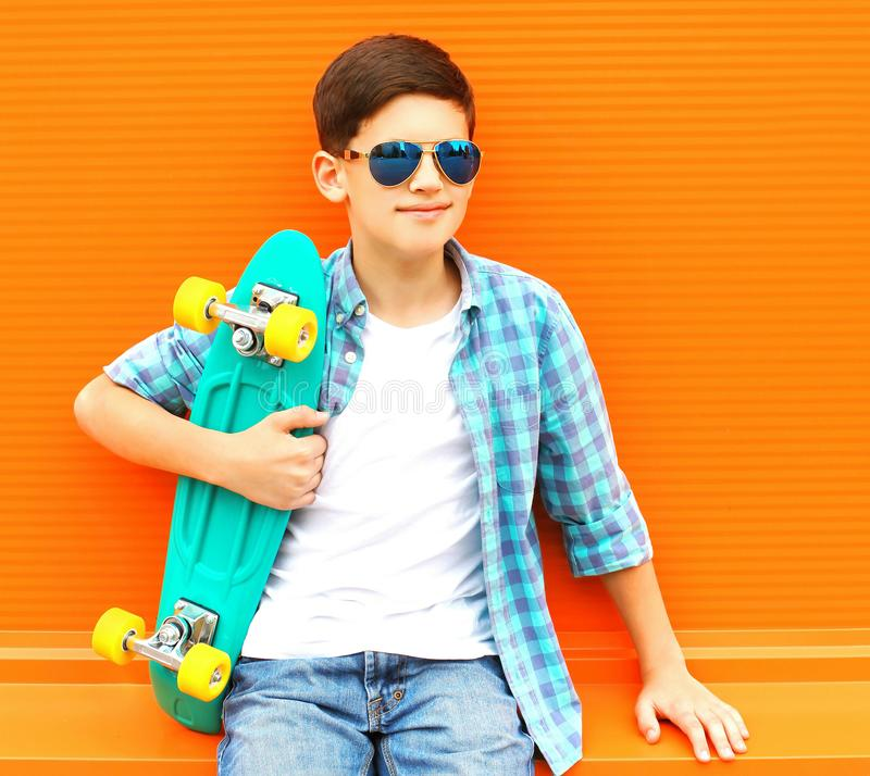 Fashion portrait teenager boy with skateboard wearing a sunglasses royalty free stock images