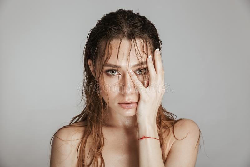 Fashion portrait of a topless attractive woman. With makeup and wet hair posing isolated over gray background stock photos