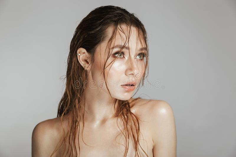 Fashion portrait of a topless beautiful woman. With makeup and wet hair posing isolated over gray background stock photos