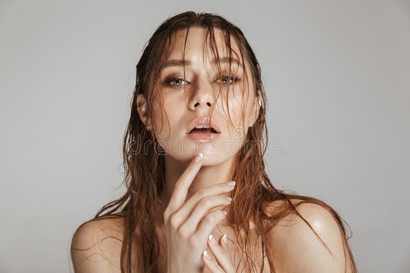 Fashion portrait of a topless beautiful woman with makeup. And wet hair posing isolated over gray background stock image
