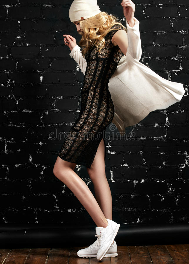 Fashion portrait of trendy girl with blond hair, wearing a black dress and jacket standing against the black urban wall royalty free stock photo