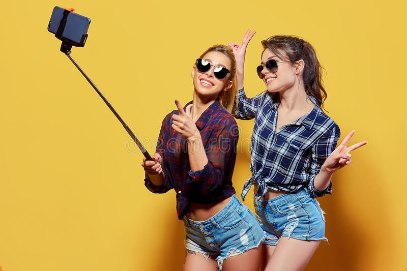 Fashion portrait of two friends posing. Fashion portrait of two friends. modern lifestyle. two stylish hipster girls best friends ready for party. Young girl royalty free stock photos