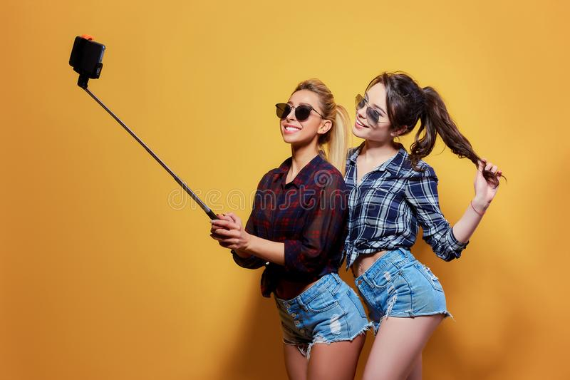 Fashion portrait of two friends posing. Fashion portrait of two friends. modern lifestyle. two stylish hipster girls best friends ready for party. Young girl royalty free stock image