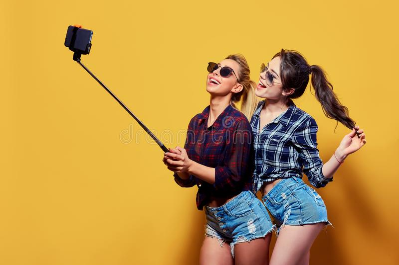 Fashion portrait of two friends posing. Fashion portrait of two friends. modern lifestyle. two stylish hipster girls best friends ready for party. Young girl stock photography