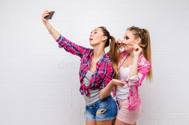 Fashion portrait of two friends posing. modern lifestyle.two stylish hipster girls best friends ready for party.Two. Young girl friends standing together and stock photo