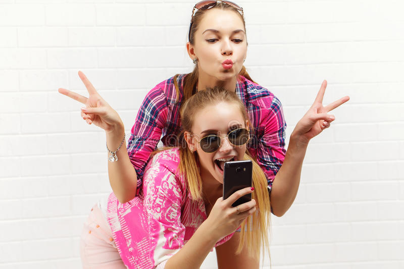 Fashion portrait of two friends posing. modern lifestyle.two stylish hipster girls best friends ready for party.Two. Young girl friends standing together and royalty free stock image