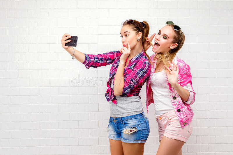 Fashion portrait of two friends posing. modern lifestyle.two stylish hipster girls best friends ready for party.Two. Young girl friends standing together and royalty free stock photos