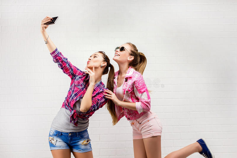 Fashion portrait of two friends posing. modern lifestyle.two stylish hipster girls best friends ready for party.Two. Young girl friends standing together and stock image