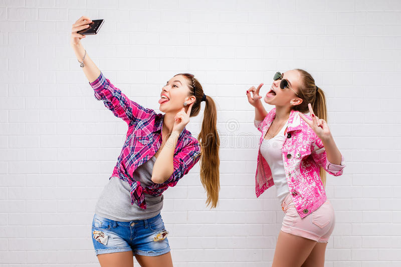 Fashion portrait of two friends posing. modern lifestyle.two stylish hipster girls best friends ready for party.Two. Young girl friends standing together and stock photos