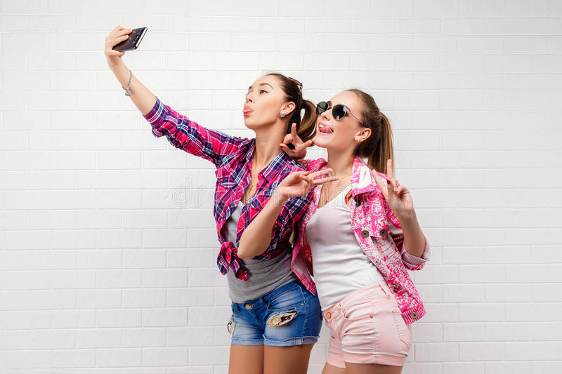 Fashion portrait of two friends posing. modern lifestyle.two stylish hipster girls best friends ready for party.Two. Young girl friends standing together and royalty free stock photography