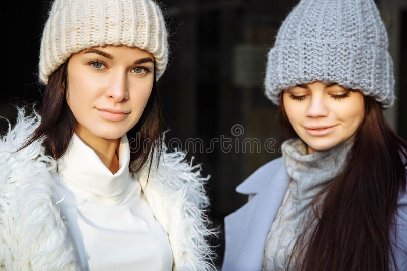 Fashion portrait of two girls friends, walking on the autumn city. stock image