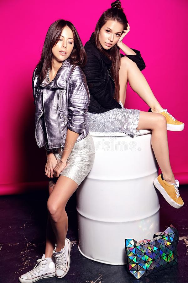 Brunette models in summer black casual hipster clothes posing on pink background royalty free stock image