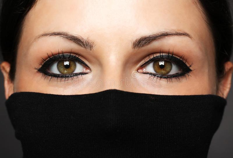 Fashion portrait of woman with hidden face with black polo neck. Look at woman eyes stock photos
