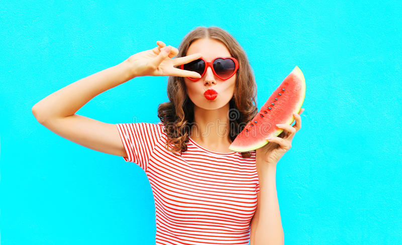 Fashion portrait woman is holding slice of watermelon and blowing lips. Over a colorful blue background royalty free stock photos