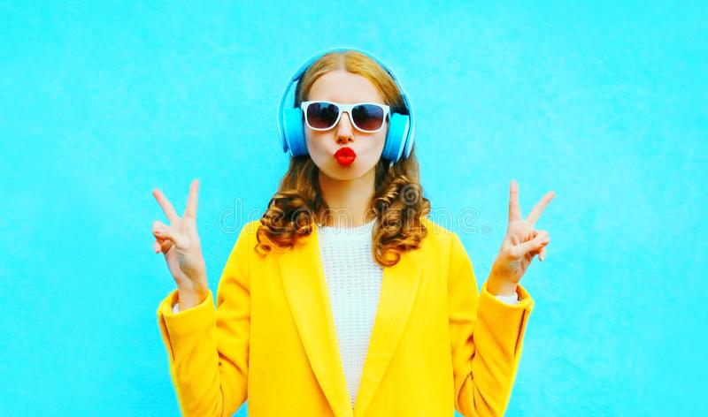 Fashion portrait woman listens to music in a headphones. On colorful blue background royalty free stock photos