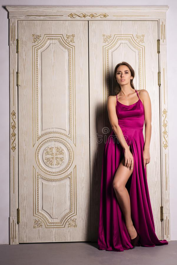 Fashion portrait of a woman posing in a beautiful evening dress, near the big white doors. Luxurious interior, perfect figure and hair girl royalty free stock photo