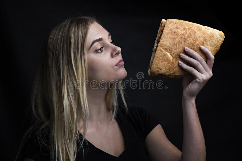 Fashion portrait of a woman with a sandwich royalty free stock images