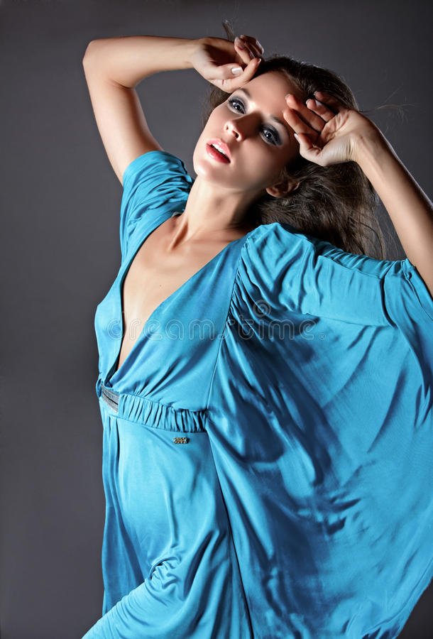 Fashion portrait of a woman in a silk blue dress. royalty free stock photography