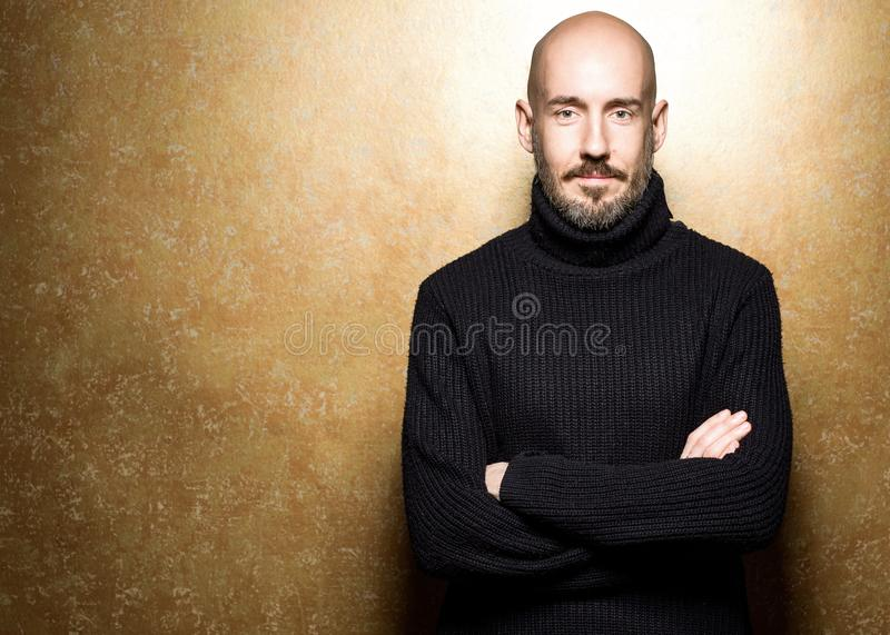 Fashion Portrait of 40-year-old man standing over light gold background in a black sweater. Close up. Classic style. Bald shaved stock photos
