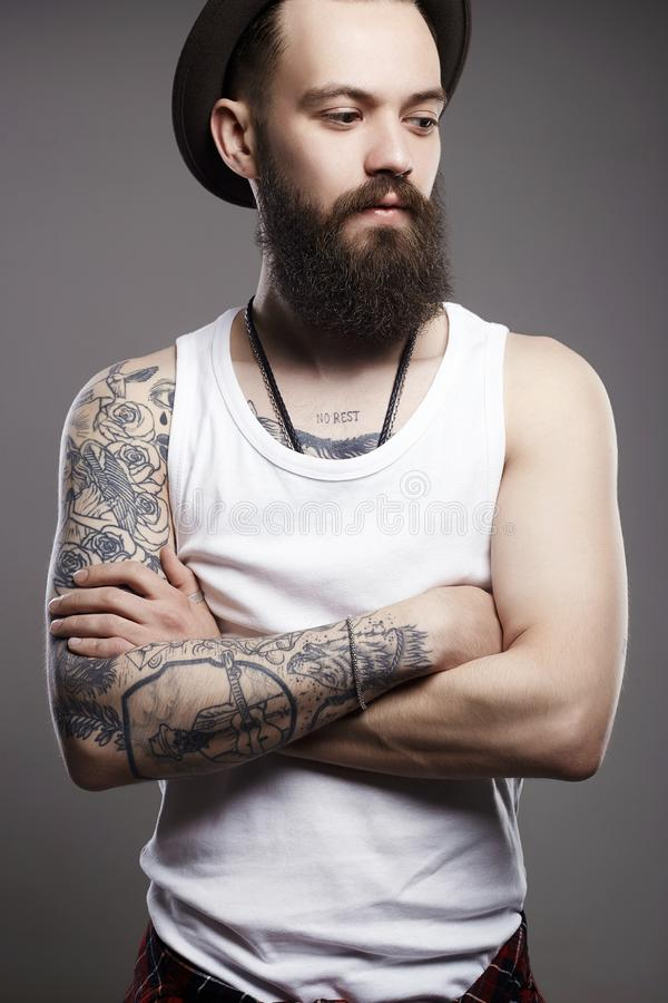 Hipster boy with tattoo. handsome man in hat. Fashion Portrait of young bearded man. Hipster boy. handsome man in hat. Brutal bearded boy with tattoo stock photos