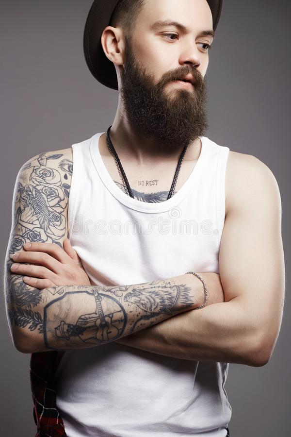 Hipster boy with tattoo. handsome man in hat. Fashion Portrait of young bearded man. Hipster boy. handsome man in hat. Brutal bearded boy with tattoo stock photography