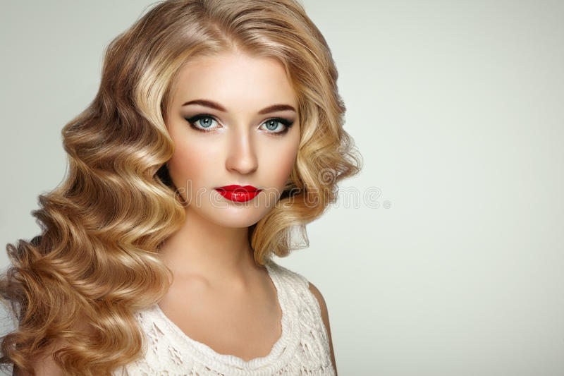 Fashion portrait of young beautiful woman with elegant hairstyle. Beautiful girl with long wavy and shiny hair . Blonde woman with curly hairstyle. Perfect make stock photos
