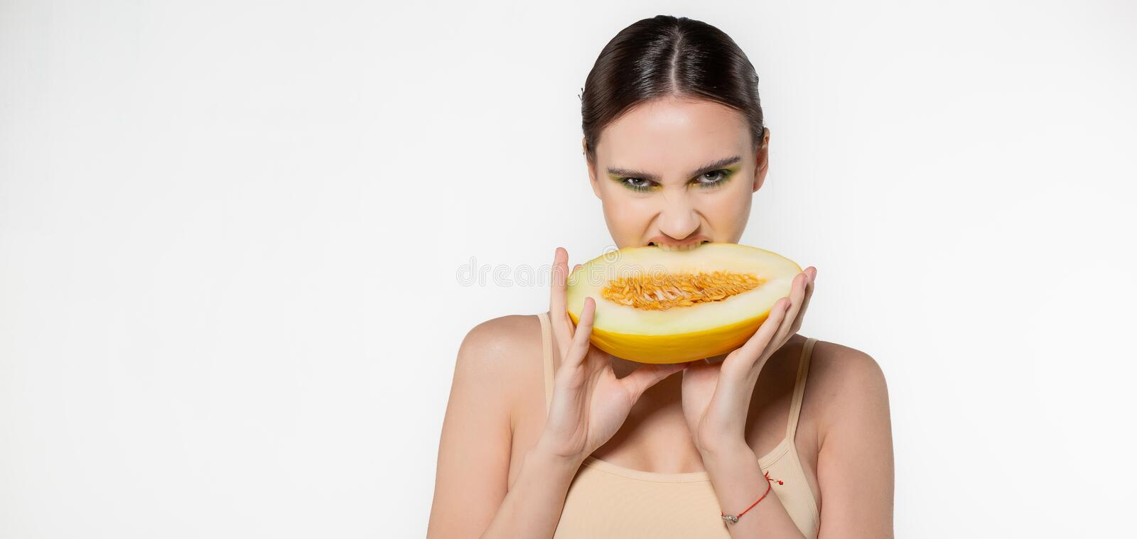 Fashion portrait of young brunette woman with green art makeup that eating sliced melon with evil eyes, copyspace for royalty free stock photos
