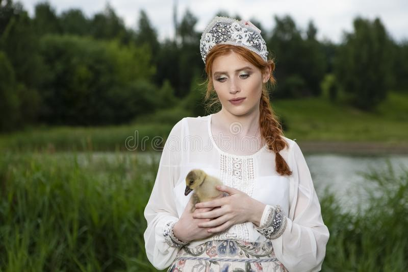 Fashion Portrait of Young Caucasian Female Posing With Duckling in Russian Style Dress and  Kokoshnik Outdoors. Horizontal Image royalty free stock photo
