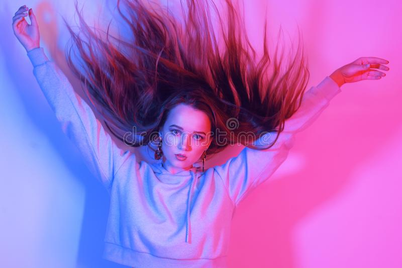 Fashion portrait of young elegant girl. Colored neon background, studio shot. Beautiful brunette woman. Hipster girl dancing in royalty free stock photography