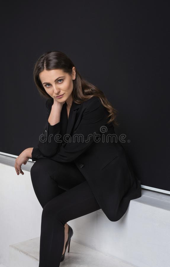 Fashion portrait of young elegant woman in black suit. Studio royalty free stock images