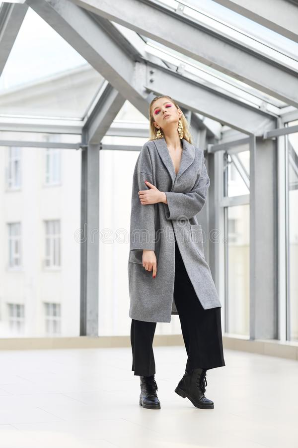Fashion portrait of young elegant woman in Grey coat, black pants, black ankle boots and gold earrings. High fashion portrait of young elegant woman in Grey coat stock photos