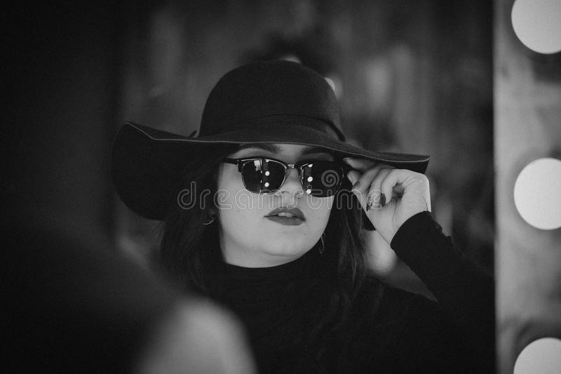 Portrait of a young girl in a hat and glasses royalty free stock image