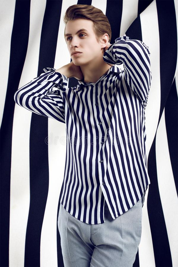 Young handsome man in striped shirt poses on black and white background royalty free stock photos