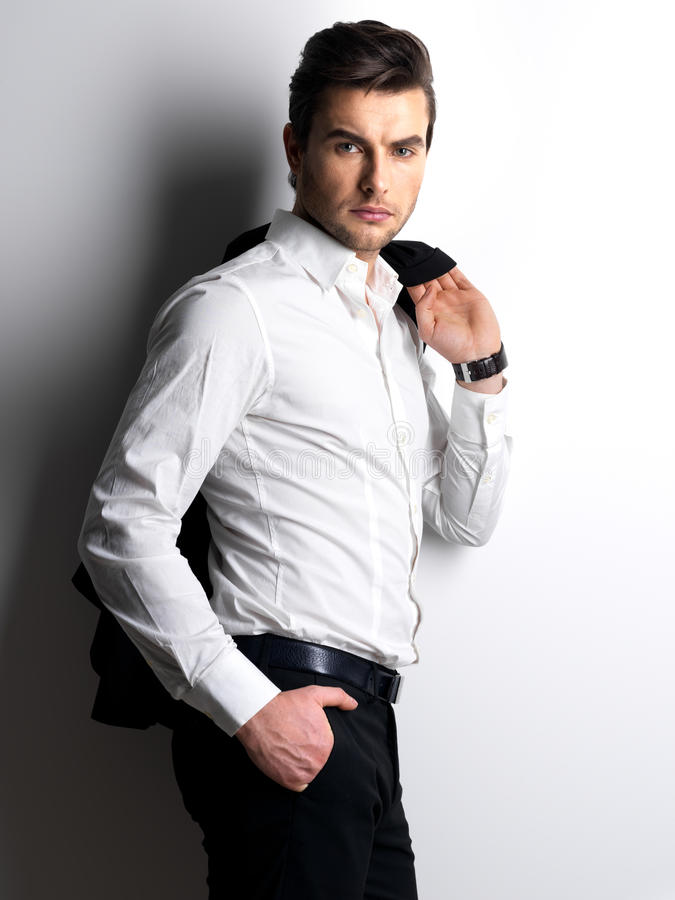 Fashion portrait of young man in white shirt. Poses over wall with contrast shadows stock photos