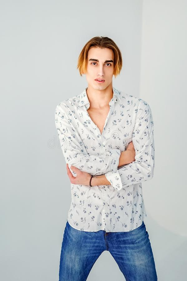 Fashion portrait of young man in white shirt poses over grey wall stock photos