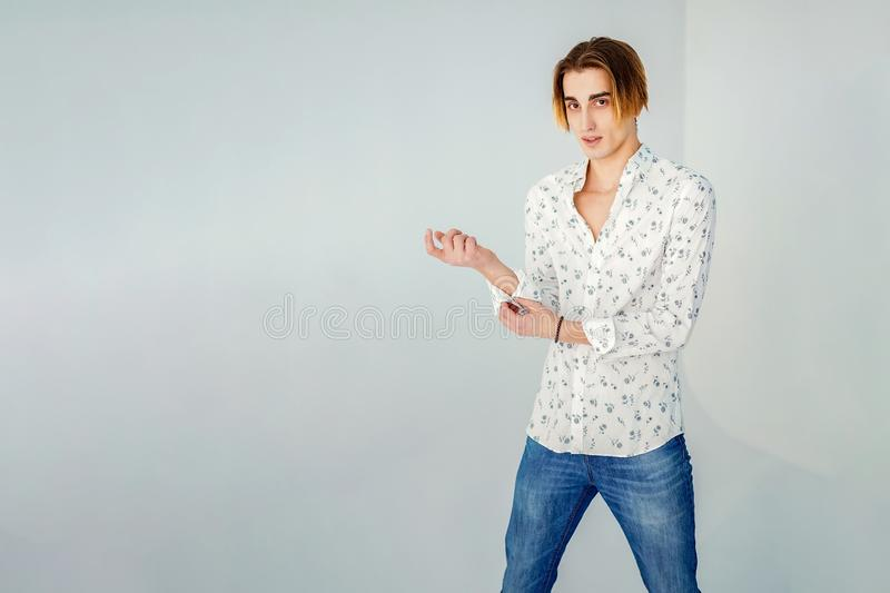 Fashion portrait of young man in white shirt poses over grey wall royalty free stock image