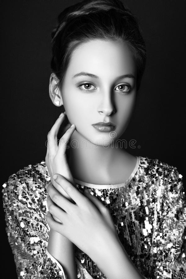 Fashion portrait. young model wearing silver evening dress. Studio black background . Black and white stock photos
