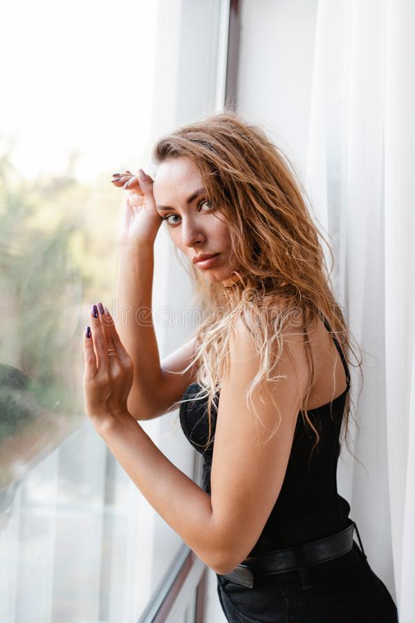 Fashion. A portrait of young slender blonde Woman in black clothes, posing leaning on the window glass stock photo