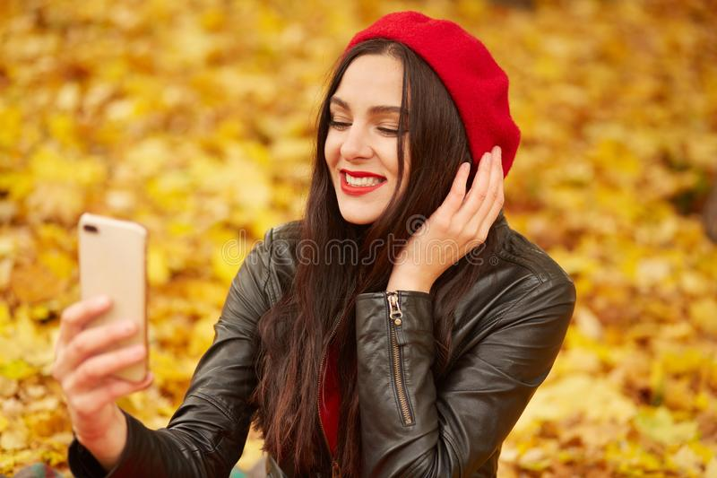 Fashion portrait of young woman outdoor in autumn park or foreest, lady wearing lather jacket, and red beret, taking self picture stock photography