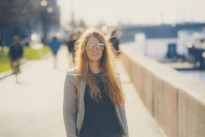 Fashion woman in sunglasses on the river embankment. outdoor portrait of young beautiful girl. Happy young smile woman sunlight ci royalty free stock photo