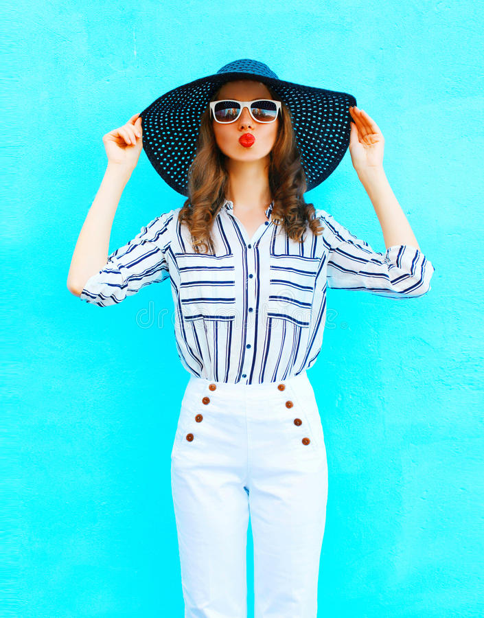 Fashion portrait young woman wearing a straw hat, white pants over colorful blue background posing in the city royalty free stock photos