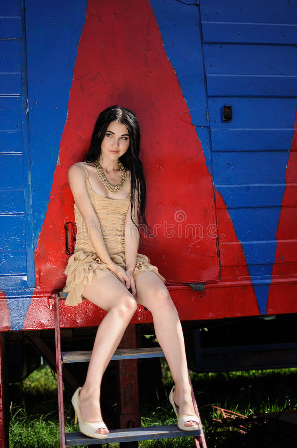 Fashion portret of beautiful girl in designer dress. Behind the scenes of the circus. On background of red-blue circus trailer royalty free stock photo
