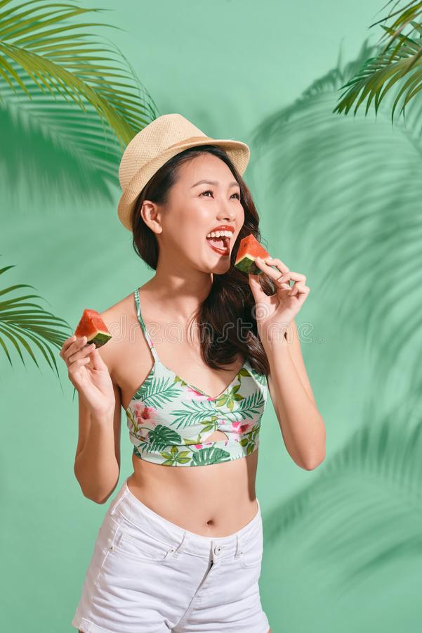 Fashion pretty asian woman is eating a slice of watermelon in the  blue background. Fashion pretty asian woman is eating a slice of watermelon in the blue stock image