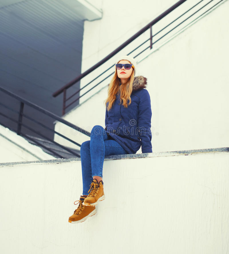 Fashion pretty blonde woman sitting in winter city over white wall stock photos