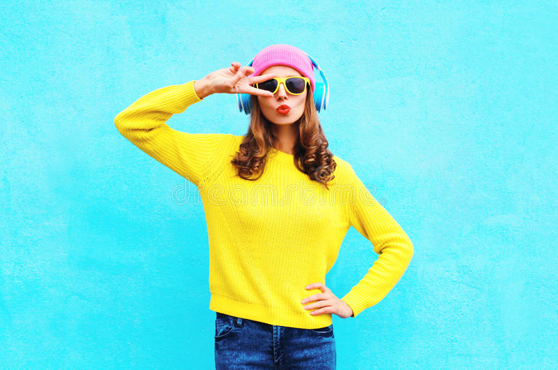 Fashion pretty cool girl in headphones listening to music wearing a colorful pink hat yellow sunglasses and sweater over blue. Background stock photography