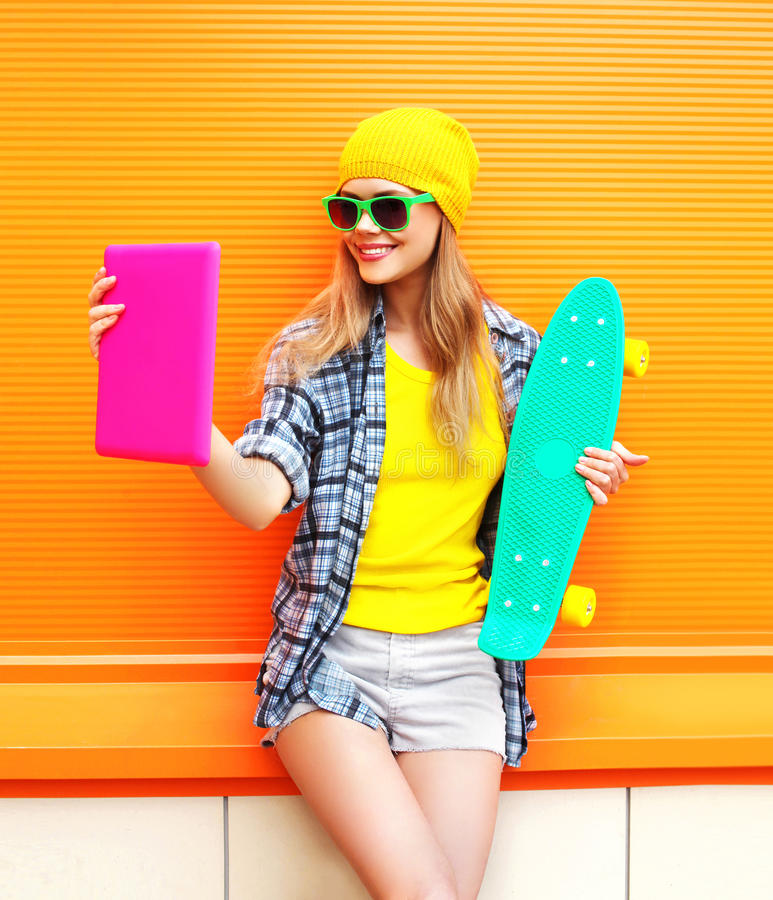 Fashion pretty cool girl makes self portrait on tablet pc over colorful orange royalty free stock photography