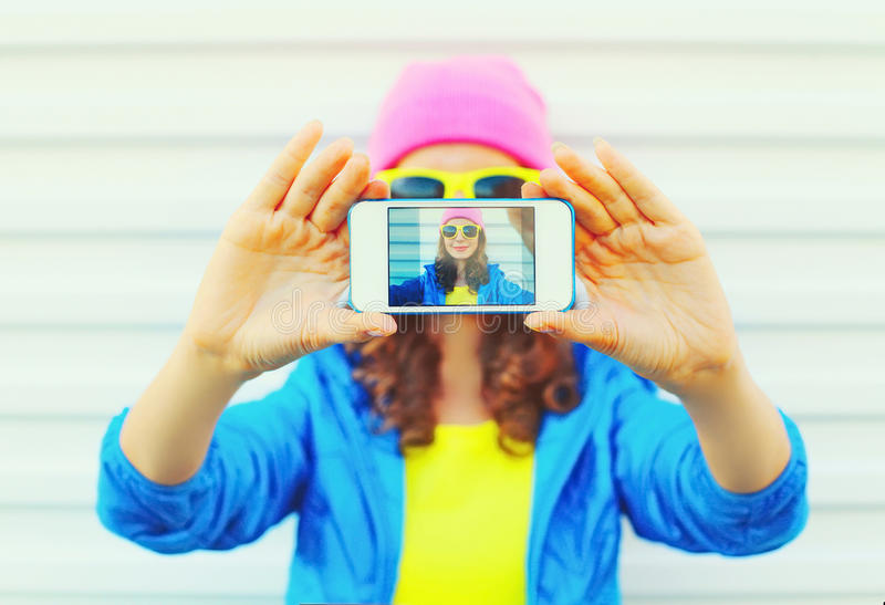 Fashion pretty cool girl taking photo self portrait on smartphone over white background wearing a colorful clothes and sunglasses. Fashion pretty cool girl royalty free stock image