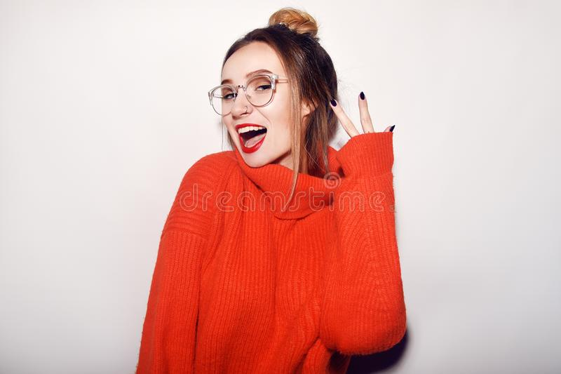 Fashion pretty cool girl wearing glasses and red sweater. Close up shot of charming female. Tender, beautiful, young. Hipster. Cut stock image